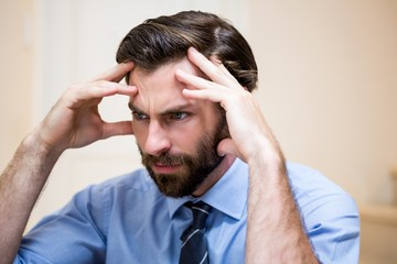 Close up of tensed man with hands on forehead
