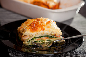 Typical Italian lasagna with spinach and salmon. Baking dish on background