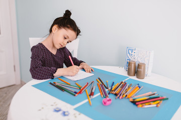 Little beautiful girl draws pencil on a table in the kitchen.