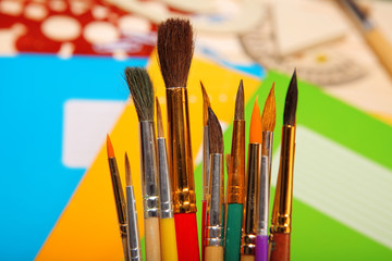 Paint brushes on exercise book background. Selective focus