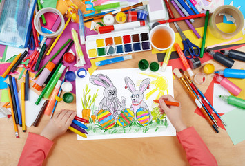 rabbit family on meadow with eggs, easter holiday concept, child drawing, top view hands with pencil painting picture on paper, artwork workplace