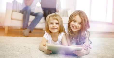 happy little girls with tablet pc computer at home