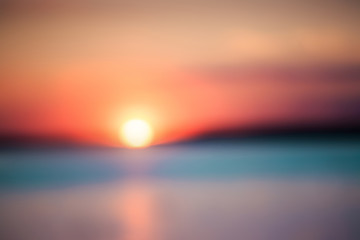 Blurry background of a picturesque view of a beautiful sunset over a river. Cloudy colorful sky.