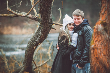 Beautiful young couple posing near lake and forest autumn. Woman in white gloves and cap.