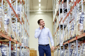 happy man calling on smartphone at warehouse