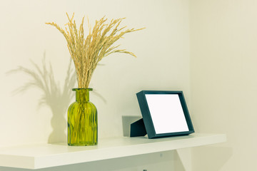 spikes of barley  inside bottle with picture frame on the shelve