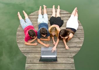 Gruppe Jugendliche mit Notebook / Laptop draußen in der Natur