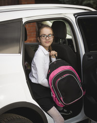 Smiling girl with school bag getting out of the car