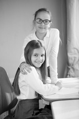 Black and white portrait of two schoolgirls posing at home