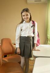 Girl with school bag standing behind desk at bedroom