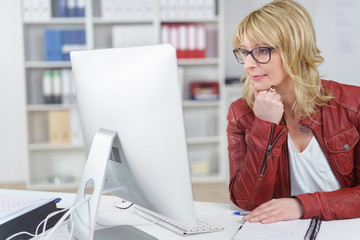 geschäftsfrau schaut mit ernstem gesicht auf computer