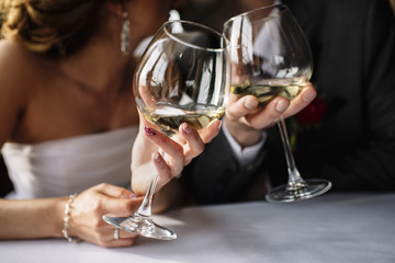 Wedding couple with glasses of wine in hands mark the wedding ceremony in the restaurant at the table. bride and groom with earrings in a dark suit blurred focus only