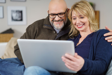 glückliches ehepaar schaut zuhause auf tablet