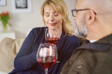 frau riecht mit geschlossenen augen an einem glas rotwein