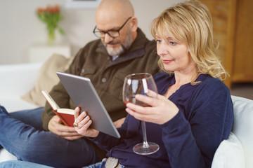 entspanntes paar genießt den abend mit lesen und einem glas wein