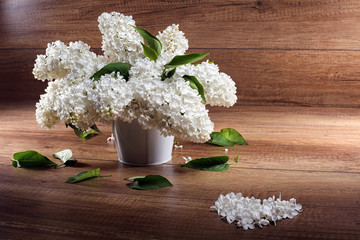 Still life. Bouquet of white lilacs in white a vase on a wooden table ,Heart with petals.