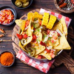 Nachos, cheese sauce, salsa and corn cobs Top view