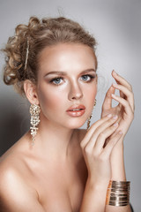 blond beauty woman portrait with golden hair jewelry and ear-rings