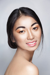 Beautiful Asian young tender woman smiles and looks in camera