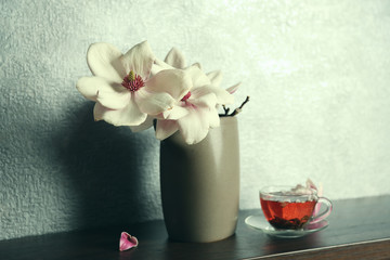 Cup of tea and magnolia on table