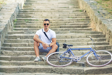 Handsome young cyclists resting on the steps of the fortress in the old town with his bicycle beside him