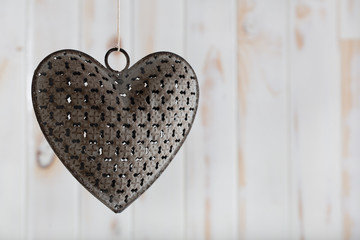 A metal heart hanging on a piece of string agains a white wooden background