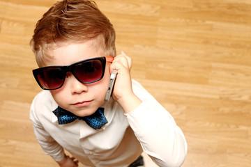 little boy looks upwards speaking on cell phone