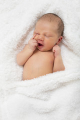 Newborn baby lying on a white blanket sleeping