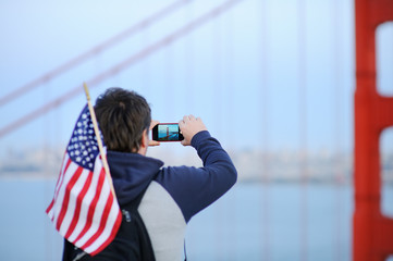 Middle age man making mobile photo on Golden Gate bridge