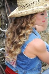 Sexy cowgirl sitting on haystacks inside a barn.