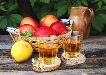Apple juice in two glass on old wooden table