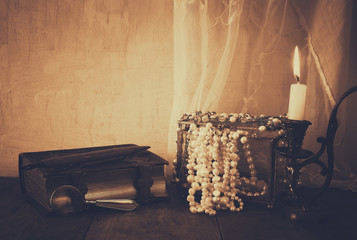 low key queen crown, white pearls next to old book