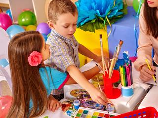 Children girl boy and  teacher woman  at table  in  kindergarten school.