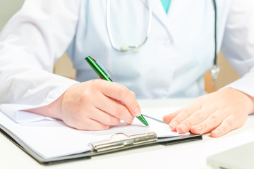 Doctor in a white coat writes on a paper prescription
