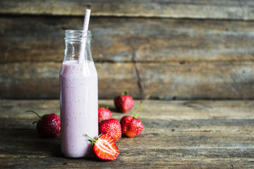 glass of strawberry smoothie and fresh strawberries on a wooden background