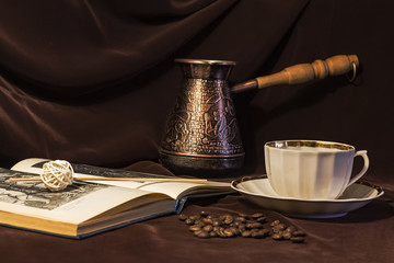 Coffee grinder, cup on the table. Brown background, still-life, tableware. Drinking coffe, book. Cezve, Ibrik brewing coffee oriental ornaments form ancient oriental emblem, dried fruits. Book