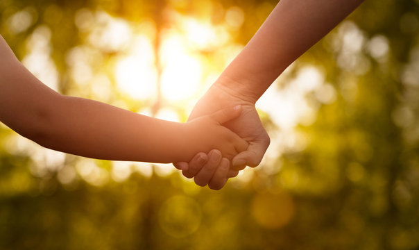 Close up of mother or older sister and a child hands at the sunset