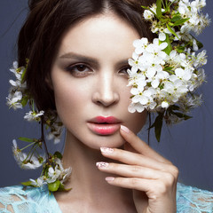 Beautiful brunette girl in blue dress with a gentle romantic make-up, pink lips and flowers. The beauty of the face.