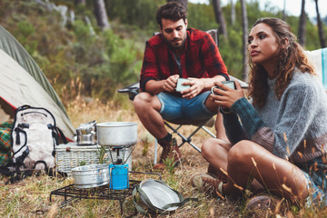 Young couple camping in nature having coffee