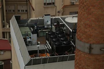 Climatización / Motores de climatización en azotea, con otros edificios de fondo, y chimenea de ladrillo en la parte derecha. Fototapete