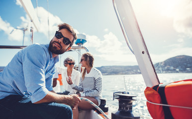 Young man sitting on the deck of a sailboat with women talking in background