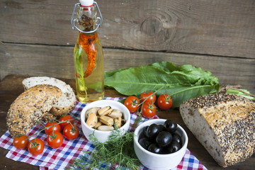 Black olives and mussels in ceramic bowls, fresh tomatoes, bread and bottle of olive oil with spices on wooden board. Mediterranean food on dark wooden background