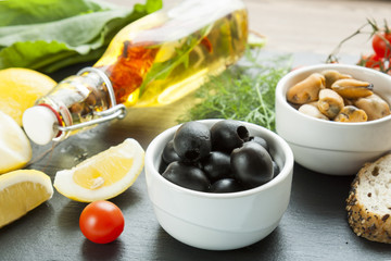 Black olives and mussels in ceramic bowls, fresh tomatoes, sliced lemon, bread and bottle of olive oil with spices on wooden board. Mediterranean food on black stone board