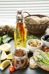 Dried tomatoes in jar and bottle of olive oil with spices, mussels and black olives and in ceramic bowls, bread, fresh tomatoes, sliced lemon, herbs on black stone board. Mediterranean food