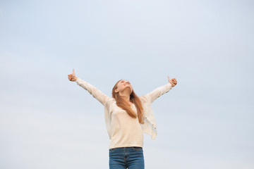 woman with open arms in the sky background at the morning