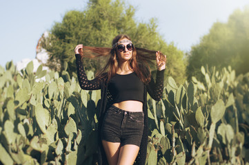 Young hippie woman with long hair standing near cactus, retro