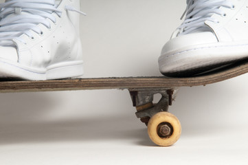 Mans feet standing on an old skateboard