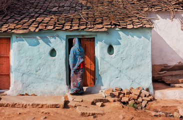 Rural house and woman in traditional sari opens the door of family home in India