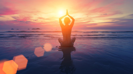 Woman yoga silhouette on the beach at amazing sunset.