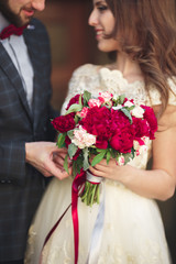 Wedding couple hugging, the bride holding a bouquet of flowers in her hand, groom embracing